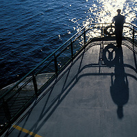 USA, Washington, Seattle, Passenger casts long shadow aboard Washington State Ferry on summer evening