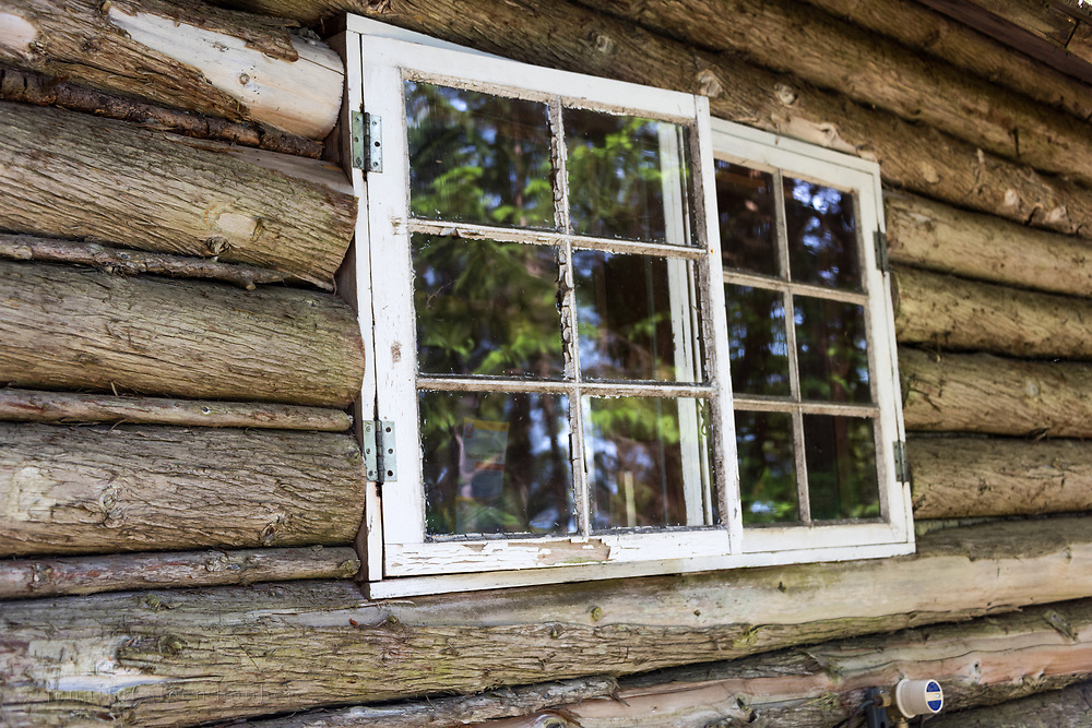 Window detail of a log cabin on Isle au Haut, Maine, USA
