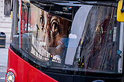 Seen reflected in the windscreen of a passing bus, a government NHS (National Heath Service) ad displays the face of a Covid patient, urging Londoners to stay at home and not to take risks or bend the rules during the third lockdown of the Coronavirus pandemic, at Piccadilly Circus in the capital's West End, on 3rd February 2021, in London, England.