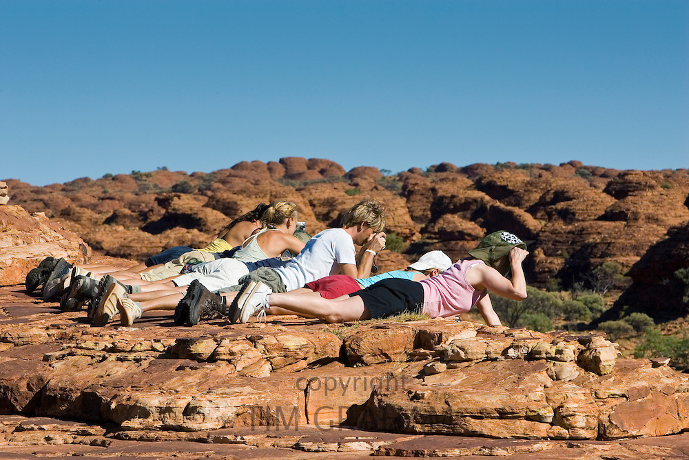 Tourists lie down to photograph King's Canyon, Red Centre, Northern Australia