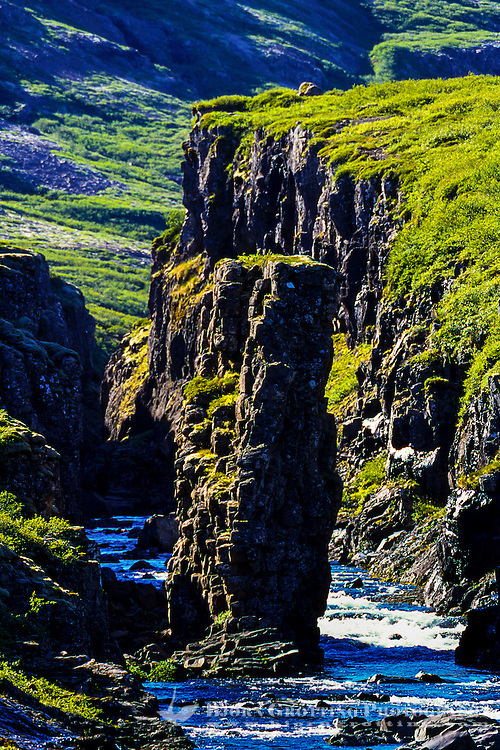 A rock formation in the middle of a river in the Westfjords in northwestern Iceland.