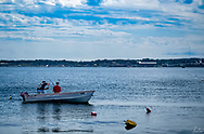 Two Fishermen in a small boat, fisihing with rods in Rockland Harbor, Rockland, Maine.