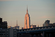 Empire State building seen in evening light from Brooklyn with the Manhattan Bridge in the foreground