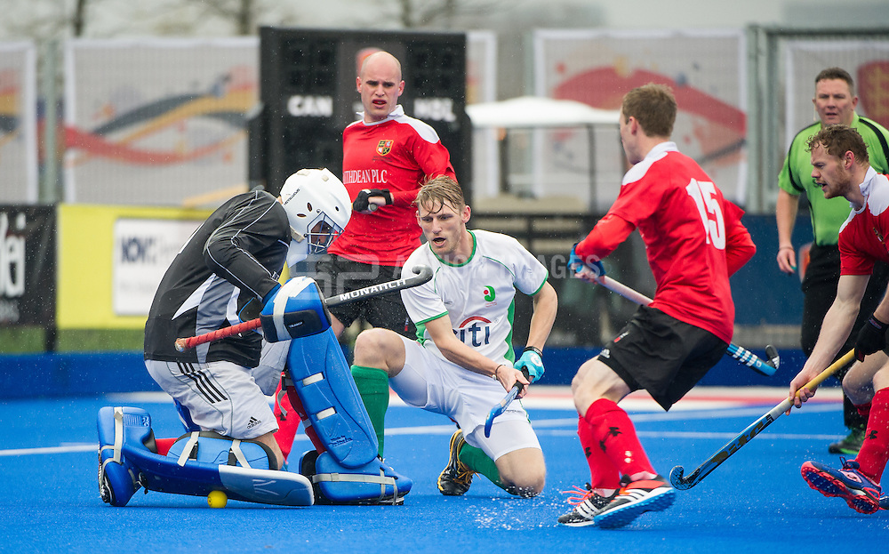 Holcombe's George Pinner tries to hide the ball. Canterbury v Holcombe - Now: Pensions Finals Weekend, Lee Valley Hockey & Tennis Centre, London, UK on 11 April 2015. Photo: Simon Parker