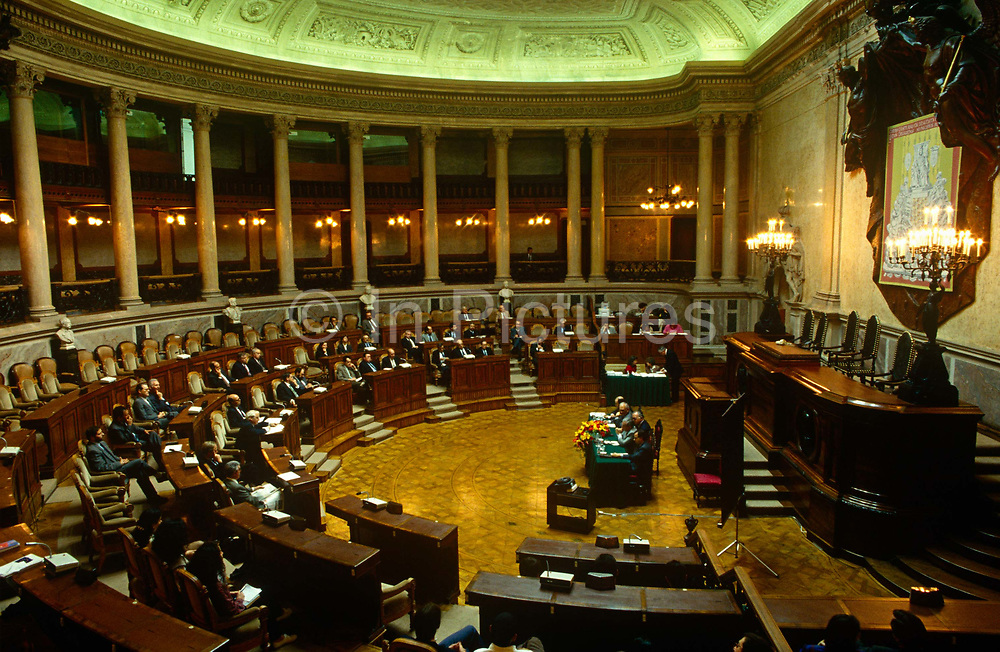 """The Portuguese parliament in session from inside the Palacio de Sao Bento in Estrela District, Lisbon. A wide interior view of this semi-circular columned chamber housing the decision makers for the Portuguese people.  The Palácio de São Bento (""""Saint Benedict's Palace"""", is the home of the Assembly of the Republic, the Portuguese parliament. It is located in Lisbon. Close to Bairro Alto, the Palace of São Bento was formerly known as the seat of the National Assembly (Assembleia Nacional) during the Estado Novo regime. Nearby is the official residence of Portugal's Prime Minister."""