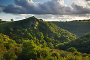 Inhabited as far back as the Stone Age, Thor's Cave dominates the Manifold Valley and rises high above its wooded slopes. The evening sun side-lights this landscape scene in the Staffordshire Peak District, England, UK.