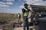 CB Barton and Leon Curley refill the tanks on their trucks at a well with safe water near Coyote Canyon Chapter in the Navajo Nation near Gallup, New Mexico.