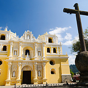 Iron cross and front of the distinctive  and ornate yellow and white exterior of the Iglesia y Convento de Nuestra Senora de la Merced in downtown Antigua, Guatemala.