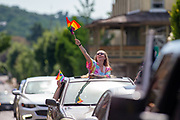 Beth Treas waves a pride flag from a car during the Mifflinburg Pride Event.