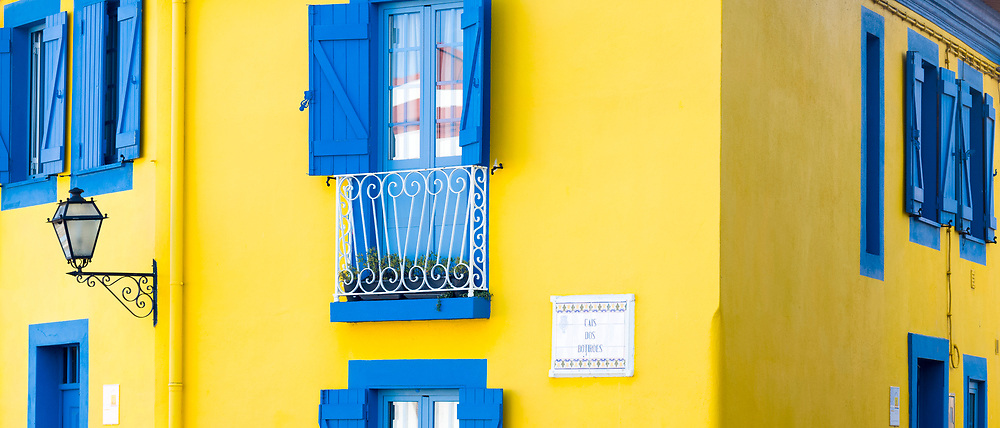 Brightly coloured blue and yellow facade, balconies, shutters, lantern in Cais dos Botiroes by the marina at Aveiro, Portugal