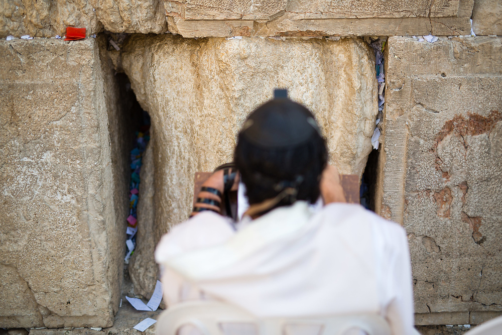Notes containing prayers and messages which were left by visitors in the cracks between the stones of the Western Wall are seen as a Jewish man prays at Judaism's holiest prayer site, in the Old City of Jerusalem, Israel, on September 17, 2017. The clean-up which takes place ahead of the upcoming Jewish New Year Holiday, clears the wall's crevices and frees up space for more notes that people of all faiths slip between its stones, believing that requests deposited at the site are more likely to be heard by God.