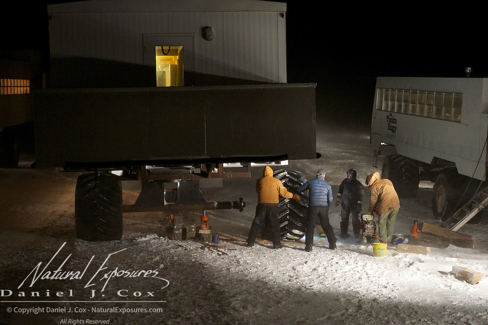 Tundra Buggy crew fixing a flat tire on the bunk house in the middle of a howling storm. Cape Churchill, Hudson Bay, Manitoba.