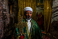 Ethiopian Orthodox priest holding a Christian cross, Bete Maryam (St. Mary's Church), one of 11 rock hewn churches in Lalibela, Ethiopia.