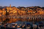 """The pretty coastal town of Menton on the French Cote d'Azur is seen beneath a cloudless blue sky in later afternoon spring sunshine. Looking across the water, in the foreground is the marina populated with assorted yachts, launches and other boats safely moored to jetties and pontoons. The bell-tower of baroque basilica Saint-Michel-Archange, houses and buildings of Menton rise up along hillsides and the mountains of the Ligurian Alps rise up in the distance, all bathed in orange light. Mediterranean Menton - near the Italian border - is known as Le perle de la France (""""The Pearl of France"""") for its famous beauty. It is also known for La Musée Jean Cocteau which is located in the town."""
