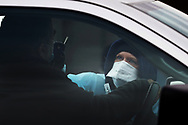 Workers from AMI Expeditionary Healthcare administer mid-nasal passage swab PCR tests to members of the public on Dec. 2, 2020, as the Pennsylvania Department of Health opened a fee, 5-day drive-thru testing site at the William Penn Highway Park & Ride in Easton, Pennsylvania.