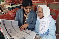 Granddaughter sitting reading a newspaper to her Sikh elderly Grandmother,