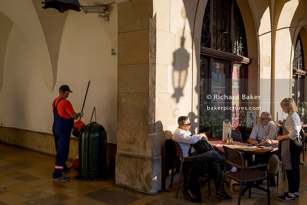 A local authority cleaner works as a priest pays the bill in afternoon sunshine in the arched passageway of the Renaissance Cloth Hall on Rynek Glowny market square, on 22nd September 2019, in Krakow, Malopolska, Poland.