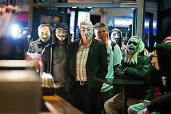 © Licensed to London News Pictures . 05/11/2015 . Manchester , UK . Protesters wearing Guy Fawkes masks sit in at a branch of Starbucks in Piccadilly Gardens at an Anonymous demonstration in Manchester , UK , this evening (5th November 2015) . Photo credit : Joel Goodman/LNP
