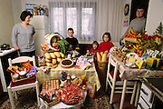 (MODEL RELEASED IMAGE). The Dudo family in the kitchen/dining room of their home in Sarajevo, Bosnia and Herzegovina, with one week's worth of food. Standing between Ensada Dudo and Rasim Dudo are their children (left to right): Ibrahim, Emina, and Amila. The Dudo family is one of the thirty families featured in the book Hungry Planet: What the World Eats (p. 46).