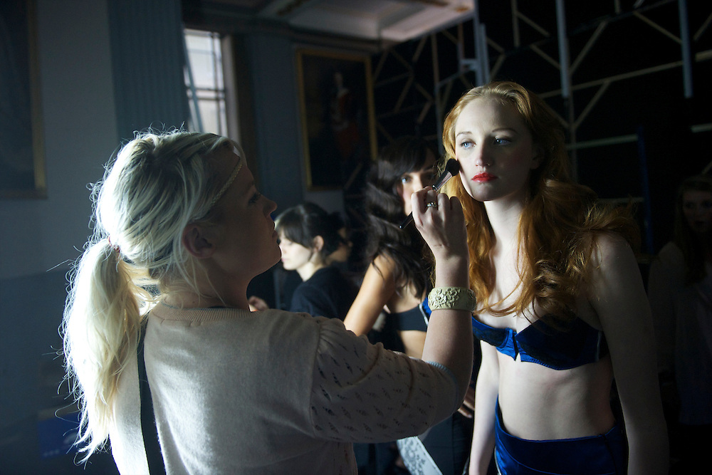 Backstage lingerie models prepare to take the catwalk at a contour design fashion show in Freemasons' Hall, London.