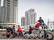 05 SEPTEMBER 2013 - BANGKOK, THAILAND:  Construction workers drink after their shift on a pile of cement water mains they are installing on the construction site of a new high rise apartment / condominium building on Soi 22 Sukhumvit Rd in Bangkok. The workers live in the corrugated metal dorms on the site. Most of the workers at the site are Cambodian immigrants.             PHOTO BY JACK KURTZ