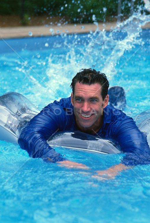 Man in a shirt playing on a float in a swimming pool