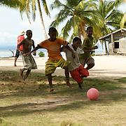 Papuan kids playing soccer.