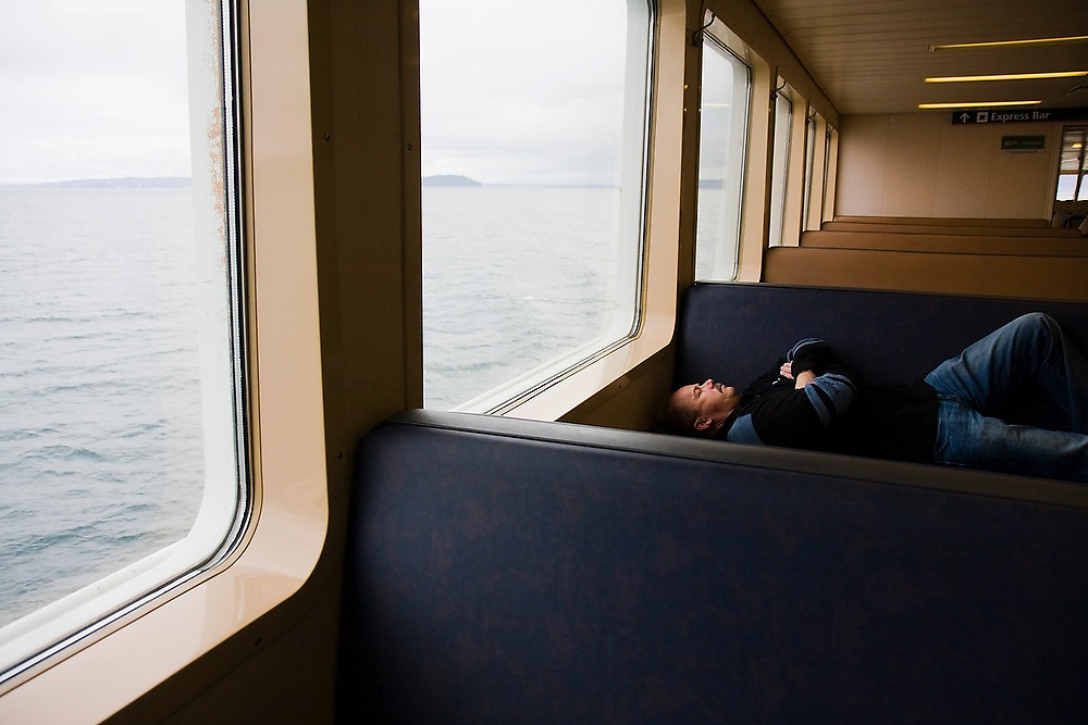 A man sleeps lying down on one of the benches during a crossing on the Edmonds Kingston ferry, which links the Seattle area to the Olympic Peninsula, Washington.