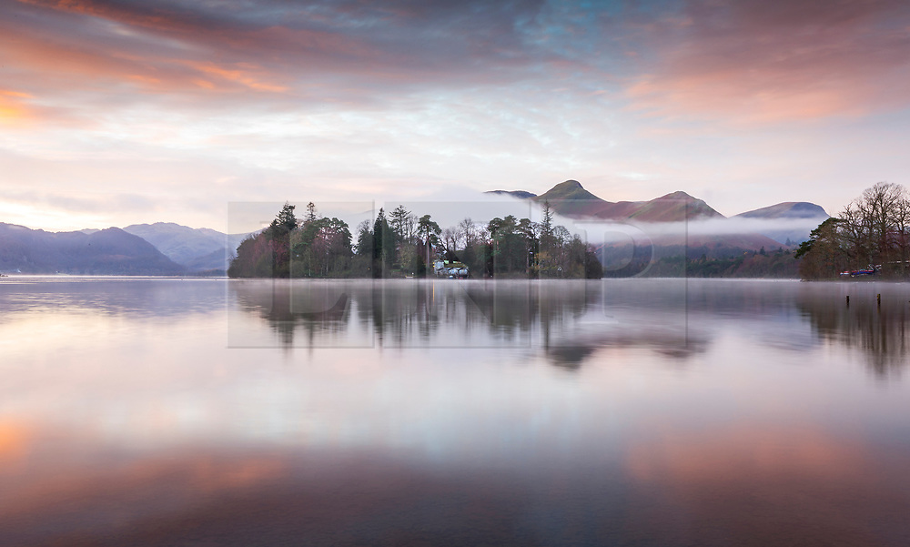© Licensed to London News Pictures. 01/12/2020. Keswick UK. The sky glows pastel orange as the sun begins to rise this morning in Keswick, Cumbria, as Derwent Isle & the surrounding mountains reflect into the calm water of Derwent Water. Photo credit: Andrew McCaren/LNP