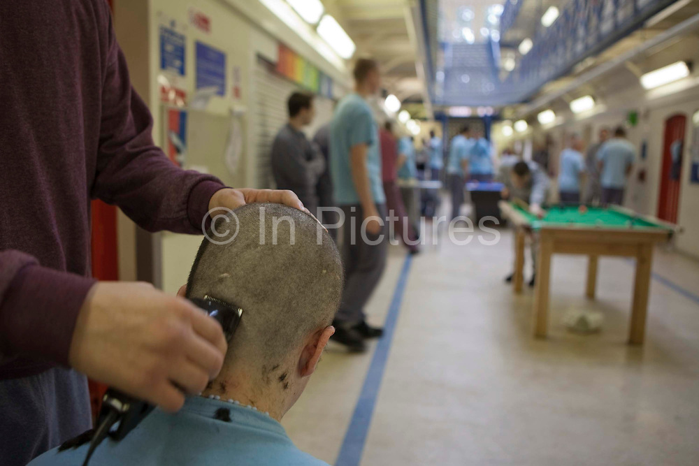 A prisoner having his hair cut by a fellow inmate during their recreation period at the Young Offenders Institution, Aylesbury, United Kingdom. HMYOI / HM Prison Aylesbury (Her Majesty's Young Offender Institution Aylesbury) is a prison is operated by Her Majesty's Prison Service.