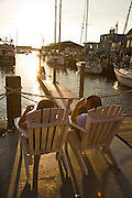 USA, Newport, RI - Couple enjoys the sunset view from adirondack chairs between Bowen's and Bannister's wharf.