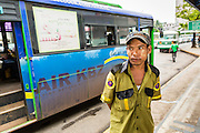 19 JUNE 2013 - YANGON, MYANMAR:  A conductor waits for passengers at a Yangon bus stop. Many of buses are imported from Japan, which drives on the left side of the road. Bus owners in Myanmar have had to cut doors into the side of the bus because Myanmar drives on the right. Yangon buses are generally overcrowded and in poor repair but as the economy improves newer, but still used, Japanese and Korean buses are being imported. Hundreds of bus routes criss-cross Yangon, providing the cheapest way of getting around the city. Most fares are less than the equivalent of .20¢ US.  PHOTO BY JACK KURTZ