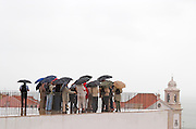 A group of tourists huddling under umbrellas in rain at the Miradouro de Santa Luzia. Street view. Alfama district. Lisbon, Portugal