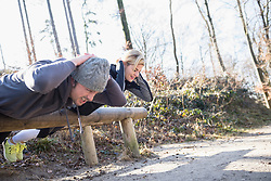 Couple doing abdominal exercise on fitness trail in nature