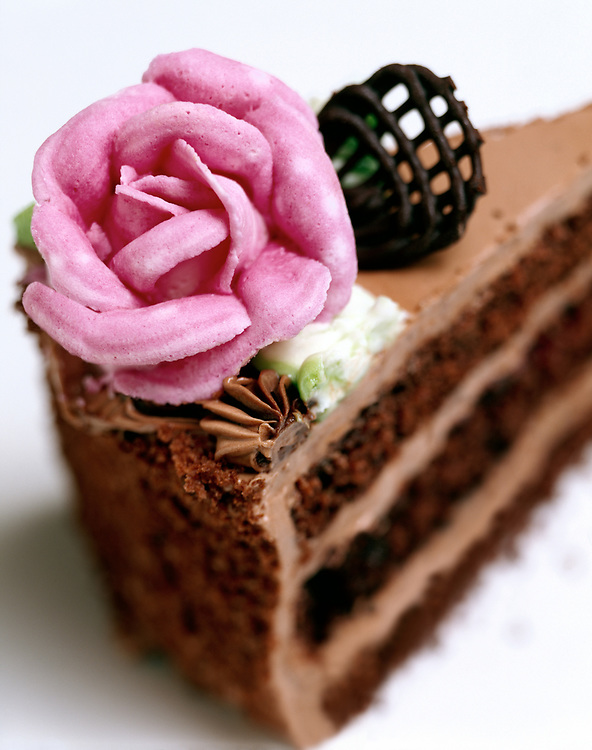 Selective focus, close up of a rose decoration on a piece of chocolate cake