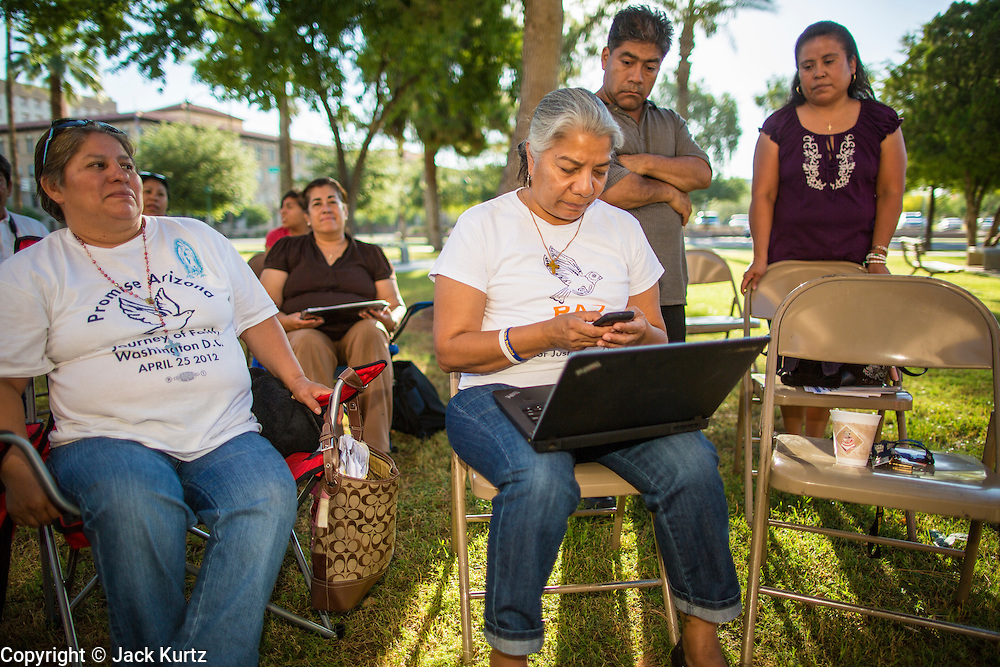18 JUNE 2012 - PHOENIX, AZ:  PETRA FALCONE, from PAZ, checks her laptop and smart phone to see if the US Supreme Court ruled on SB1070 Monday. About 20 people, members of the immigrant rights' group Promise AZ (PAZ) held a prayer vigil at the Arizona State Capitol in Phoenix Monday praying that the US Supreme Court would overturn SB 1070, Arizona's controversial anti-immigrant law. The court's ruling had been expected Monday, June 18 but the the court said the ruling would not come out until later this month. Members of PAZ said they would continue their vigil until the ruling was issued.   PHOTO BY JACK KURTZ