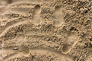 Footprints in the sand of a couple hugging. The feet are facing one another.????? ?????? ?? ??? ?????? ????