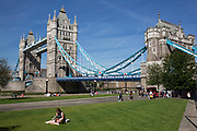 Summertime in London, England, UK. Woman reading near to Tower Bridge at Potters Fields Park. This newly created green space is now popular with tourists and others to come for a summer rest with this great iconic landmark as the backdrop.