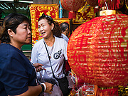 "18 JANUARY 2017 - BANGKOK, THAILAND: People shop for Chinese New Year lanterns in Bangkok's Chinatown district. Chinese New Year, also called Lunar New Year or Tet (in Vietnamese communities) starts Saturday, 28 January. The coming year will be the ""Year of the Rooster."" Thailand has the largest overseas Chinese population in the world; about 14 percent of Thais are of Chinese ancestry and some Chinese holidays, especially Chinese New Year, are widely celebrated in Thailand.      PHOTO BY JACK KURTZ"
