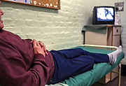 An elderly inmate passes time by watching TV in his cell on the Vulnerable Prisoners Unit. HM Prison Wandsworth is a Category B men's prison at Wandsworth in the London Borough of Wandsworth, South West London, United Kingdom. It is operated by Her Majesty's Prison Service and is one of the largest prisons in the UK with a population over 1500 people. (photo by Andy Aitchison)