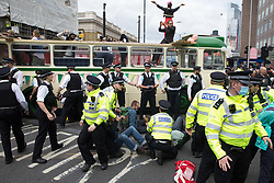 London, UK. 31st August, 2021. Metropolitan Police officers intervene as environmental activists from Extinction Rebellion use a vintage bus as a base to block a road junction to the south of London Bridge on the ninth day of their Impossible Rebellion protests. Extinction Rebellion are calling on the UK government to cease all new fossil fuel investment with immediate effect.
