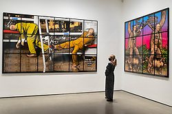 """© Licensed to London News Pictures. 12/04/2021. LONDON, UK. A staff member views """"Priority Seat"""" and """"Pigging"""", both 2020, by Gilbert & George at the opening of their """"NEW NORMAL PICTURES"""" exhibition at White Cube's Mason's Yard gallery in Mayfair. The exhibition displays 26 pictures from a new series the pair have been working on for over two years.  The UK government's coronavirus roadmap out of lockdown has allowed art galleries to reopen today. The exhibition runs 13 April to 8 May 2021.  Photo credit: Stephen Chung/LNP"""