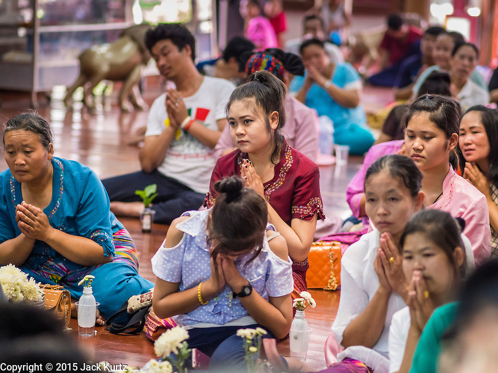 """06 APRIL 2015 - CHIANG MAI, CHIANG MAI, THAILAND:  Family members in the prayer hall at Wat Pa Pao during the ordination of the boys on the last day of the three day long Poi Song Long Festival in Chiang Mai. The Poi Sang Long Festival (also called Poy Sang Long) is an ordination ceremony for Tai (also and commonly called Shan, though they prefer Tai) boys in the Shan State of Myanmar (Burma) and in Shan communities in western Thailand. Most Tai boys go into the monastery as novice monks at some point between the ages of seven and fourteen. This year seven boys were ordained at the Poi Sang Long ceremony at Wat Pa Pao in Chiang Mai. Poy Song Long is Tai (Shan) for """"Festival of the Jewel (or Crystal) Sons.  PHOTO BY JACK KURTZ"""