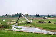 Nederland, Andelst, 23-4-2019 De herinrichting van het nieuwe natuurgebied de Loenensche Buitenpolder in opdracht van Rijkswaterstaat en Staatsbosbeheer is in uitvoering. Nieuwe riviernatuur wordt gemaakt door het maken van nieuwe poelen en geulen die na doorsteken van de zomerdijk, de oever, in verbinding staan met de rivier de Waal.   Martens en van Oord is de uitvoerder van dit omvangrijke waterproject in het kader van ruimte voor de rivier . Waterschap rivierenland, provincie Gelderland, gemeente Overbetuwe en stichting Waalweelde participeren .Foto: Flip Franssen