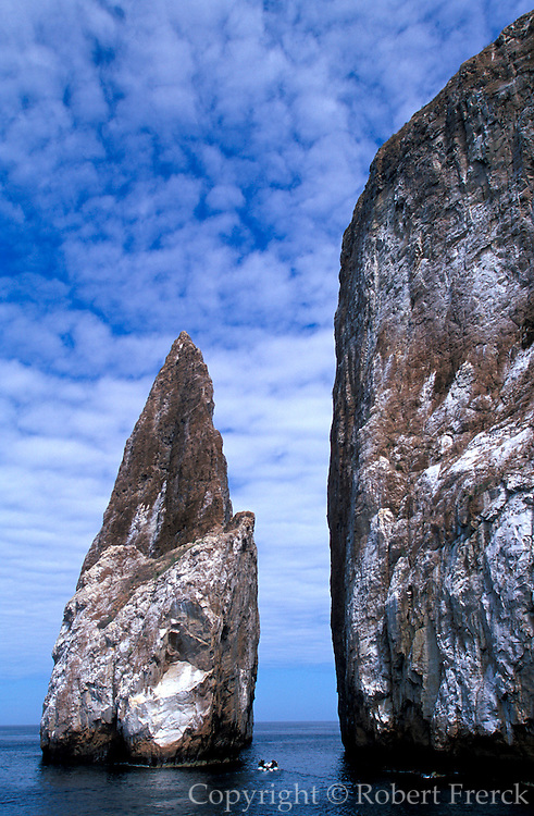 ECUADOR, GALAPAGOS ISLANDS a dive boat passes between two spectacular  volcanic plugs called Kicker Rock,  located off San Cristobal Island,