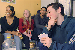 Multiracial group of teenage boys and girls sitting together drinking alcohol and playing game of cards,
