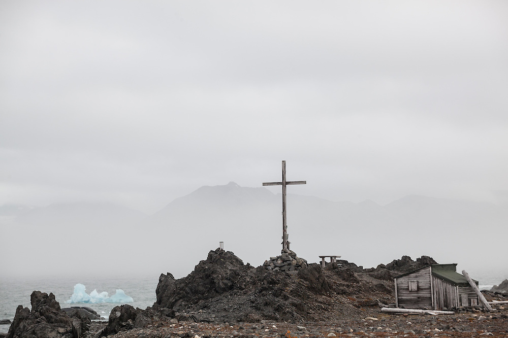 A wooden cross and a historic shelter on the coast outside the Polish Polar Station in Hornsund, Svalbard.