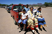 At the end of a Sunrise Dance, the first menstruaton rite of an Apache girl, on the San Carlos Apache Reservation, Arizona, USA, a caravan of pickups loaded with gifts travel from the camp of the family of the girl to the camp of her godparents. Girls dressed in camp dress and moccasins sit on the platform of the last pickup. The Sunrise Dance is the most important ceremony of the Apache Indians. It is held during the summer, within one year after the girl has had her first menstruation, and lasts for four days. The rites are supposed to prepare the girl for adulthood and to give her a long and healthy life without material wants.