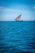 A small sail fishing boat on the sea between Stone Town and Changuu Island Zanzibar, Tanzania.