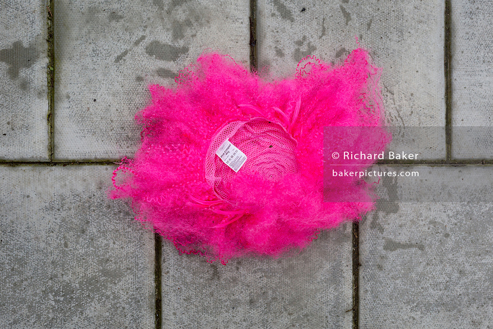 Detail of a discarded pink party wig left on the pavement of a residential street, on 10th February 2019, in London, England.